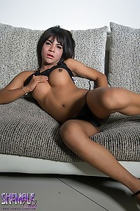Yaya in a hot black dress strokes her huge throbbing dick on the sofa