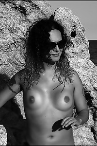 Nikki strips off naked in a spanish beach exposing her nice tits and give her dick a splash
