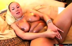 Plump ebony shemale in pink lingerie oils up her huge tits
