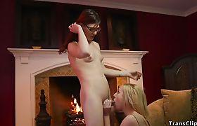 Blonde sucks tranny beside fireplace