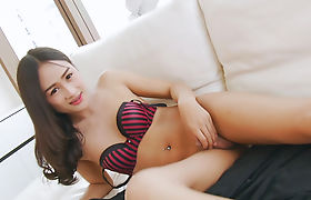 Cutie asian tranny strokes her tiny cock on the couch